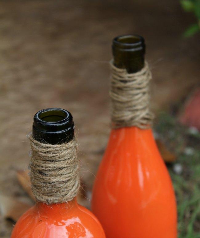 Paint wine bottle to look like pumpkins